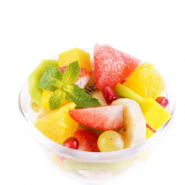 Healthy fruit salad in the glass bowl over white background